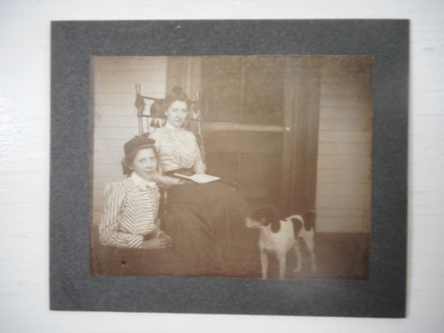 Image for Photograph; Young Girl with Older Woman Readng on Porch with Dog